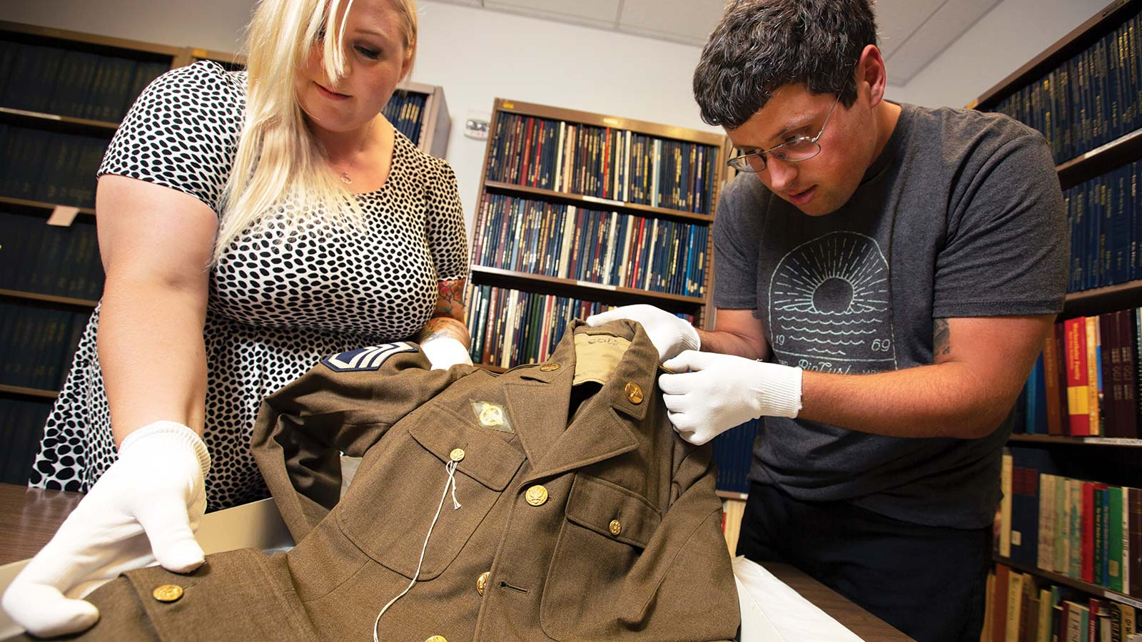 Students examining soldier uniform.